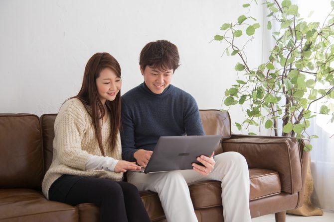 夫婦でPCを見ている写真